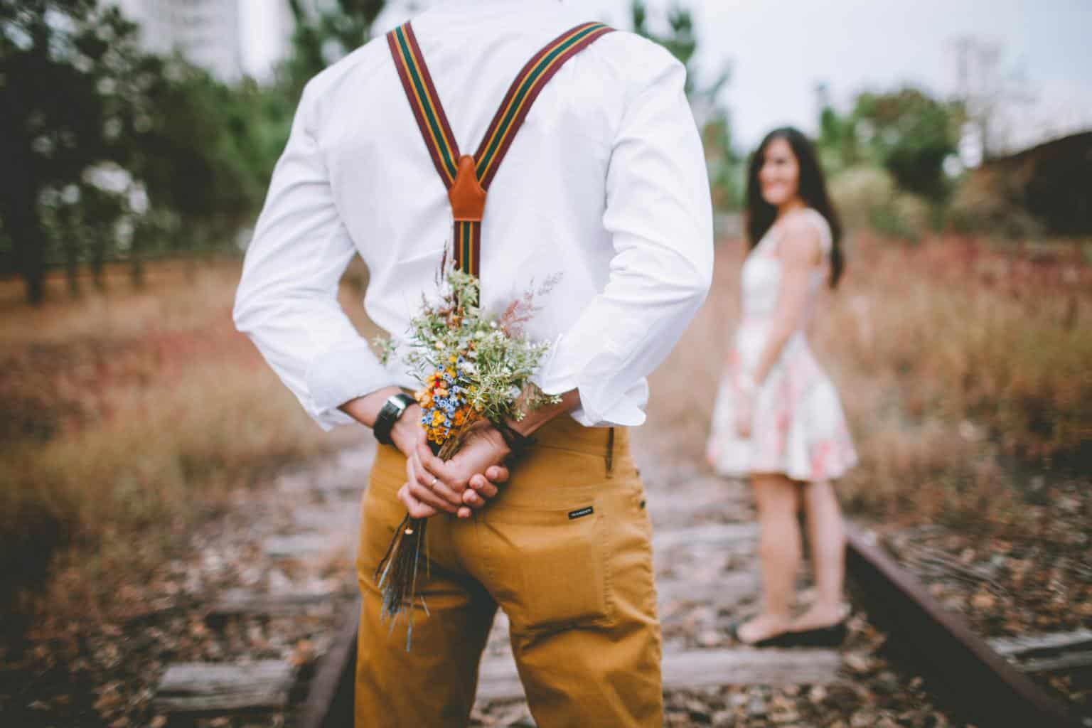 husband hiding flowers behind his back for his wife