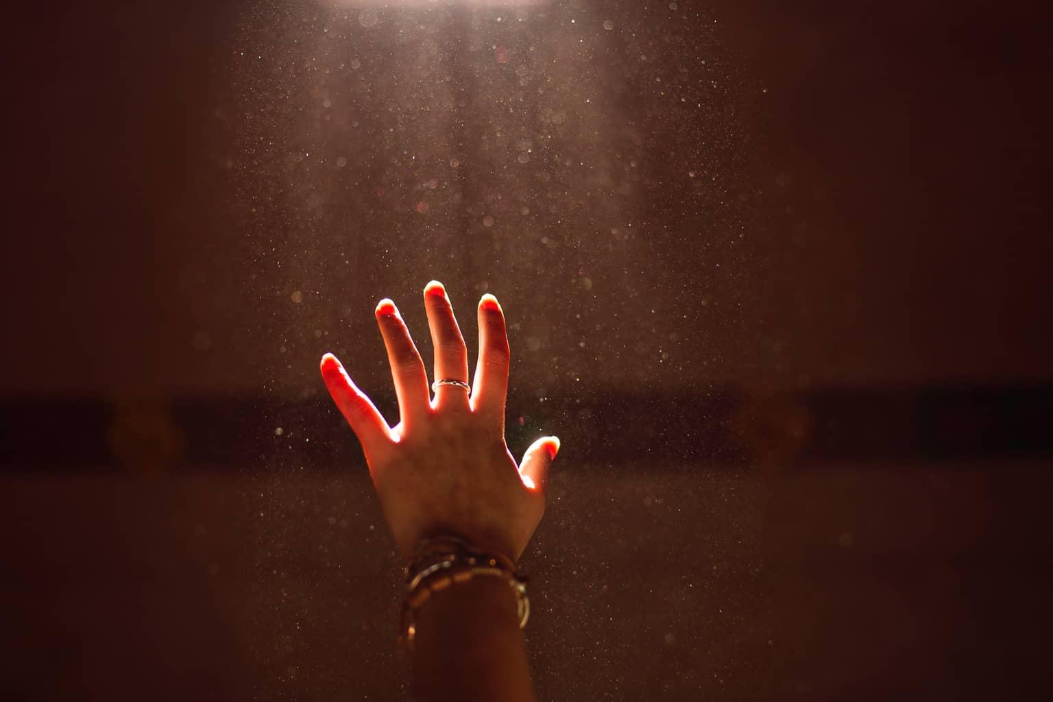 worship hand reaching up towards light