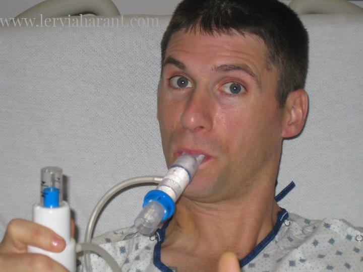young male surgery patient using a spirometer