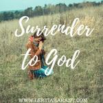woman kneeling in field praying in surrender to God